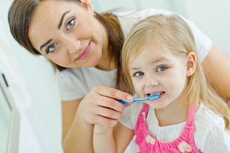 Mom and Daughter brushing their teeth - Pediatric Dentist in Madison, MS